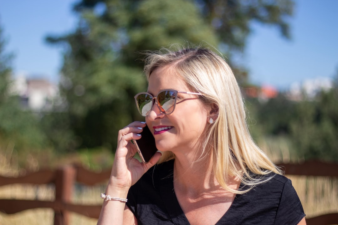 A woman wearing glasses talking on a cell phone